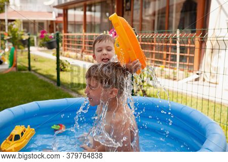 Two Children With Toys At Swimming Pool. Joyful Kid Playing In Inflatable Pool On The Backyard. Litt