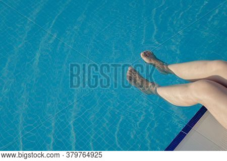 Cropped Young European Woman Kicks In The Pool Splashes Water. Concept, Carefree, Summer, Vacation.