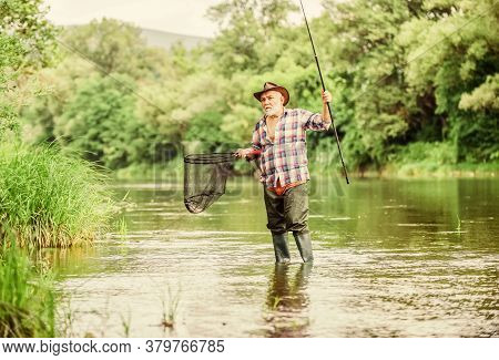 Mature Man Fishing. Retired Fisherman. Fisherman With Fishing Rod. Activity And Hobby. Fishing Fresh