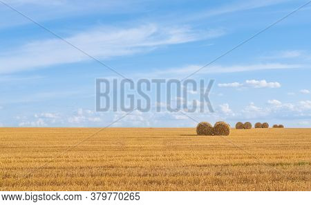 Haystacks At A Field. Rural Landscape Against The Blue Sky. Hay Bales And Field Stubble. Rhythmic Ph
