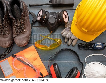 Work Safety Protection Equipment Background. Industrial Protective Gear On Wooden Table