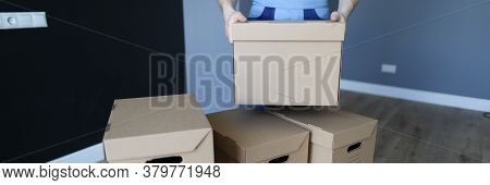 Loader Stacks Cardboard Boxes In An Empty Room. Moving Packed, Property In Separate Boxes. Man In Wo