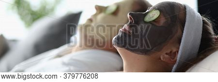 Man And Woman Lie With Mask Their Faces Cucumbers. Couple Lying On Bed With Cosmetic Mask On Face. R