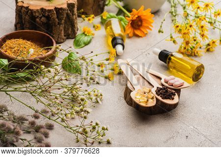 Selective Focus Of Wildflowers, Herbs, Bottles And Pills In Wooden Spoons On Concrete Background, Na