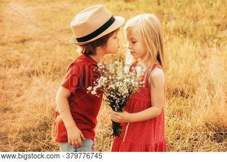 Kids Love Concept. Children Having Kiss In Autumn Field. Little Couple Kissing And Enjoying At Count