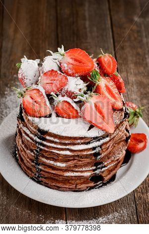 Stack Of Pancakes With Strawberries, Chocolate And Icing Sugar