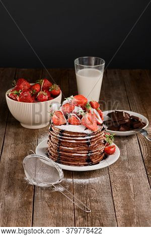 Pancakes With Strawberry And Chocolate On Wooden Table