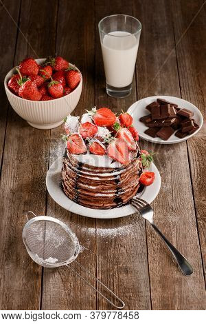 Pancakes, Strawberries, Chocolate And Glass Of Milk On Wooden Table