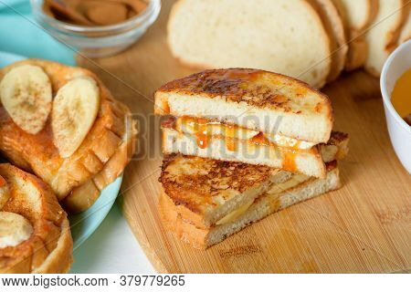 French Toast With Banana And Homemade Caramel With Cinnamon, Breakfast Dessert On A Blue Plate On A
