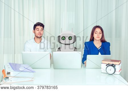 Young Man And Woman Corporate Employees With Laptops Sitting At Table With Robot Colleague And Peeki