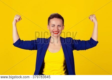 I Am Powerful Concept. Portrait Of A Happy Elegant Business Woman Showing Power Her Biceps On Yellow