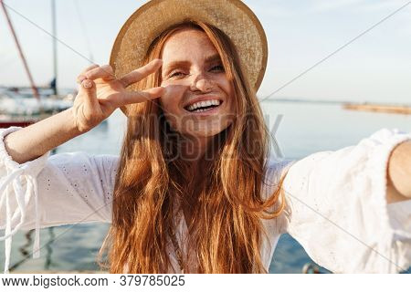 Image of cheerful woman gesturing peace sign and taking selfie photo while walking on promenade