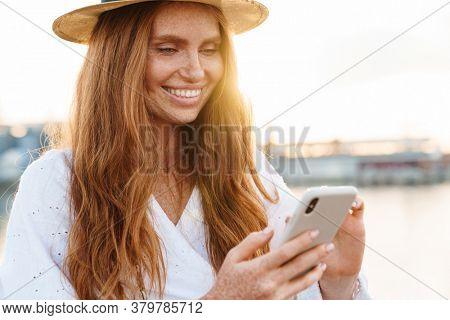 Image of joyful woman smiling and using mobile phone while walking on promenade