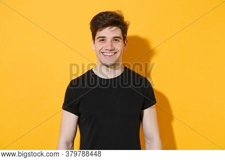 Smiling Handsome Young Man Guy Wearing Casual Black T-shirt Posing Isolated On Yellow Wall Backgroun