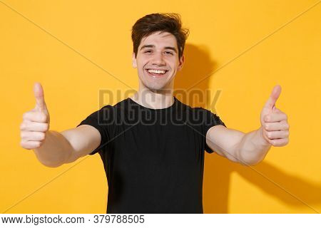 Cheerful Young Man Guy 20s Wearing Casual Black T-shirt Posing Isolated On Yellow Wall Background St