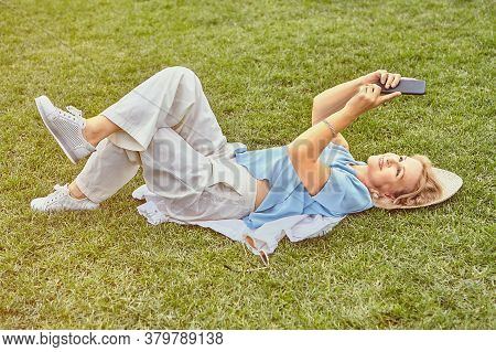 Aged Attractive White Woman About 62 Years Old In Casual Elegant Cloth Is Lying Down The Grass In Th