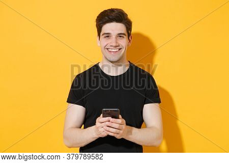 Smiling Young Man Guy 20s In Casual Black T-shirt Posing Isolated On Yellow Background Studio Portra