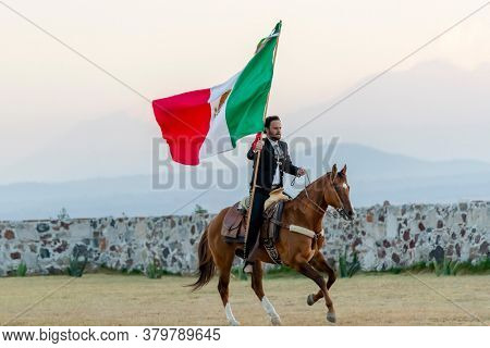A handsome Mexican Charro poses in front of a hacienda in the Mexican countryside while holding the Mexican Flag