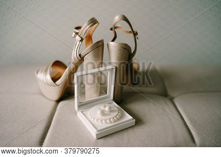 Mother-of-pearl High-heeled Platform Sandals And A Box With A White Bead Bracelet And Earrings On A
