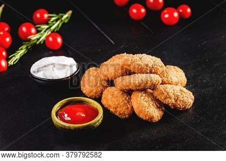 Fried Chicken Nuggets With Sauce, Tomatoes And On A Dark Background. Fast Food Concept