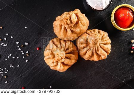 Appetizing Traditional Fried Khinkali On A Dark Background Among And Sauces. Traditional Food Concep