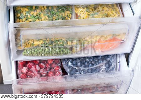 Plastic Bags With Different Frozen Vegetables In Refrigerator. Vegetables On The Freezer Shelves