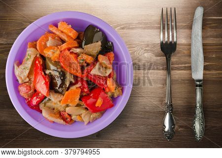 Vegetable Stew On Brown Wooden Background. Stew In Bulgarian On Purple Plate With Fork And Knife Top