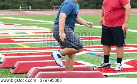 A High School Football Lineman Is Running An Agility Drill Over Red Barriers Ahile The Coach Is Watc