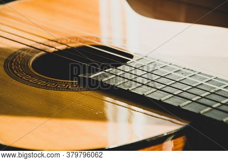 Close-up Of Guitar Strings In Sunlight. Guitar Fretboard Part, Acoustic Six-string Wooden Guitar, St