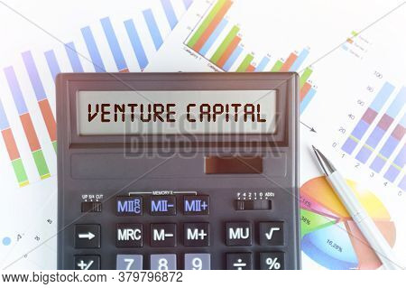 The Concept Of Business And Finance. On The Table Are Financial Charts And A Calculator, On The Elec
