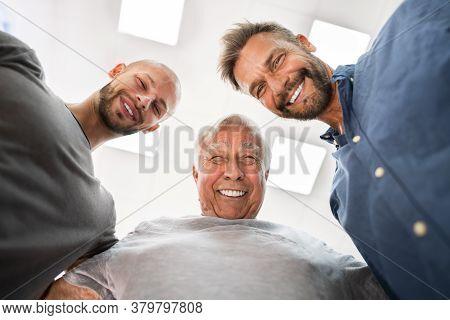 Three Generation Happy Men Standing Making Huddle