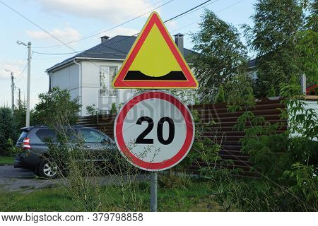 Two Road Signs A Speed Bump And A Speed Limit On The Street By The Road In Green Vegetation