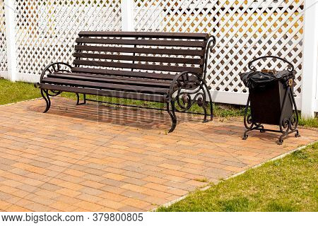 An Empty Dark Wooden Bench Next To A Metal Trash Can On The Background Of A White Plastic Fence In A