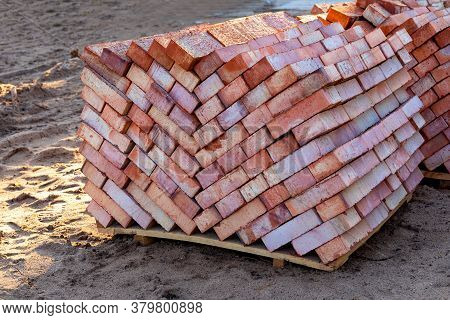 Racks With Full-bodied Bricks. Several Pallets Of Red Bricks Are Stacked On Top Of Each Other. Mater