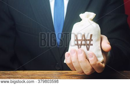 A Businessman Holds In His Hand A South Korean Won Money Bag. Stimulating Economic Recovery. Investm