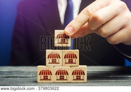 A Man Builds A Pyramid From Blocks Of Business Shops. Building A Successful Business Empire. Expansi
