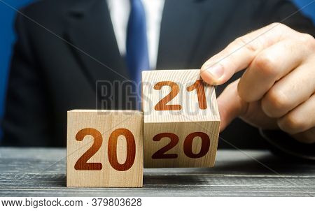 Hand Flips A Block Changing 2020 To 2021. New Year Beginning. Holidays And Christmas. Trends And Cha