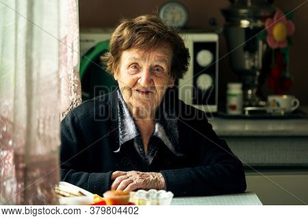 Portrait of senior woman in the kitchen in her village house.