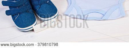 Pregnancy Test With Positive Result And Clothing For Newborn On Boards, Concept Of Extending Family