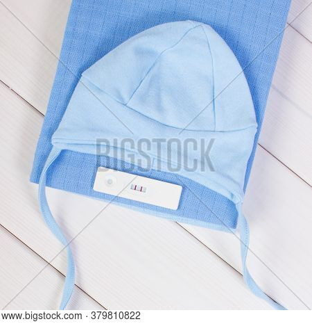 Pregnancy Test With Positive Result And Clothing For Newborn, Concept Of Extending Family And Expect