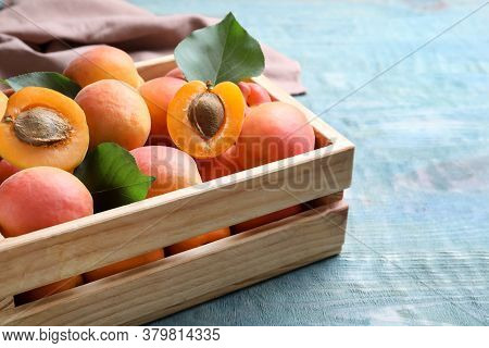 Delicious Fresh Ripe Apricots In Crate On Blue Wooden Table, Closeup