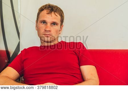Serious Sad Handsome Blond Man In Casual Style Red T-shirt Sit Look At Camera, Waiting Someone, Thin