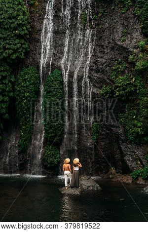 Lovers At The Waterfall. Couple Admiring A Beautiful Waterfall In Indonesia. Couple On Vacation In B