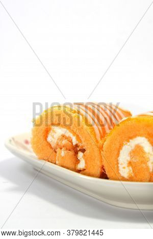 Orange Jam Roll Cake Is A Snack With Tea Or Coffee On A White Background. Use Lights And Flash For C