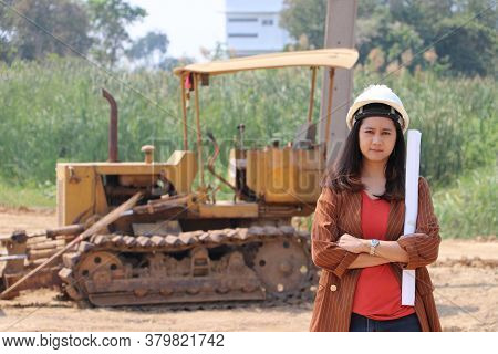 Female Civil Engineer Or Architect Wear The White Helmet Cross One's Arm And Project Drafts While In
