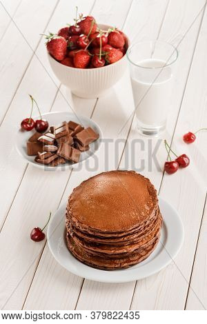 Pancakes, Chocolate, Berries And Milk On White Rustic Table