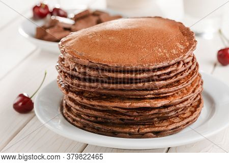 Huge Pile Of Brown Pancakes Served With Cherries, Chocolate And Glass Of Milk