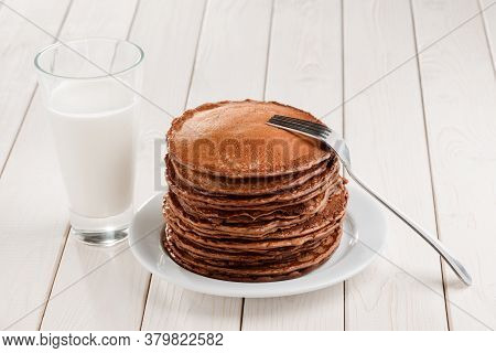 Pile Of Thick Brown Pancakes, Fork And Glass Of Milk