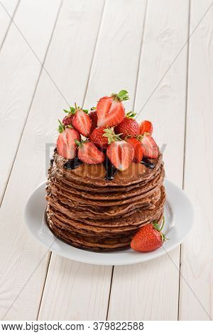 Big Portion Of Pancakes Adorned With Chocolate Topping And Strawberry Halves