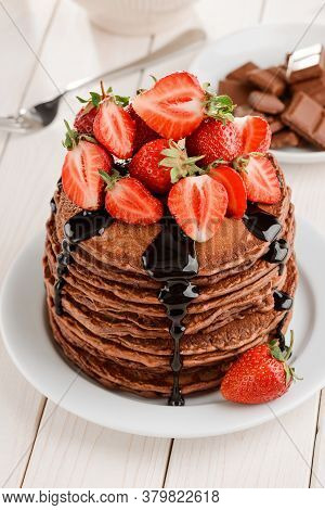 Fresh Strawberries And Chocolate Topping On A Pile Of Pancakes